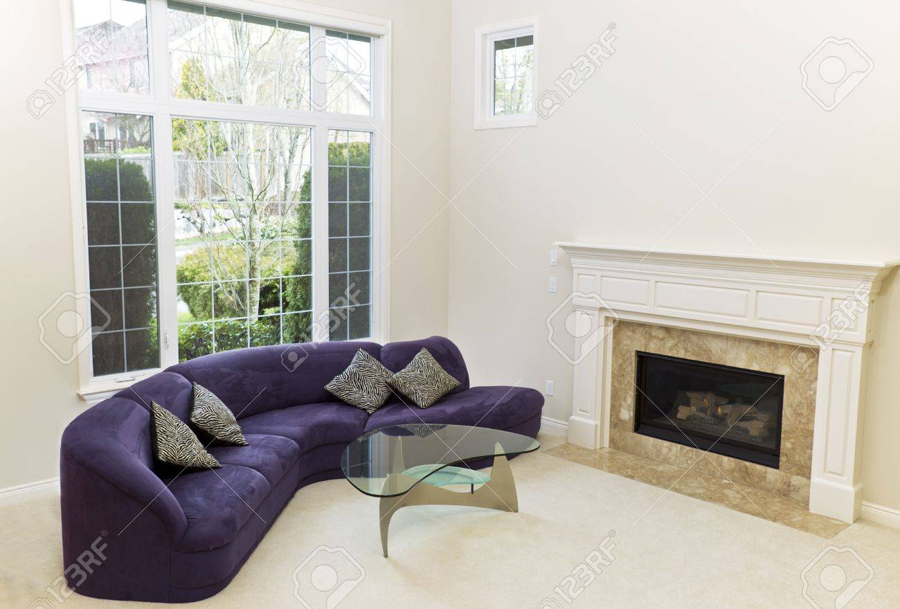 Living room with sofa, glass table, fireplace and carpet floors..