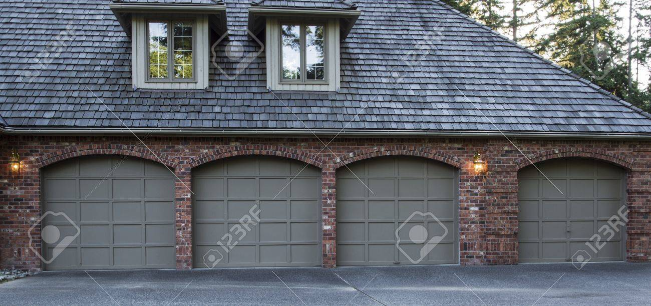 Four Car Garage Doors Made Of Wood And Brick With Trees And Sky