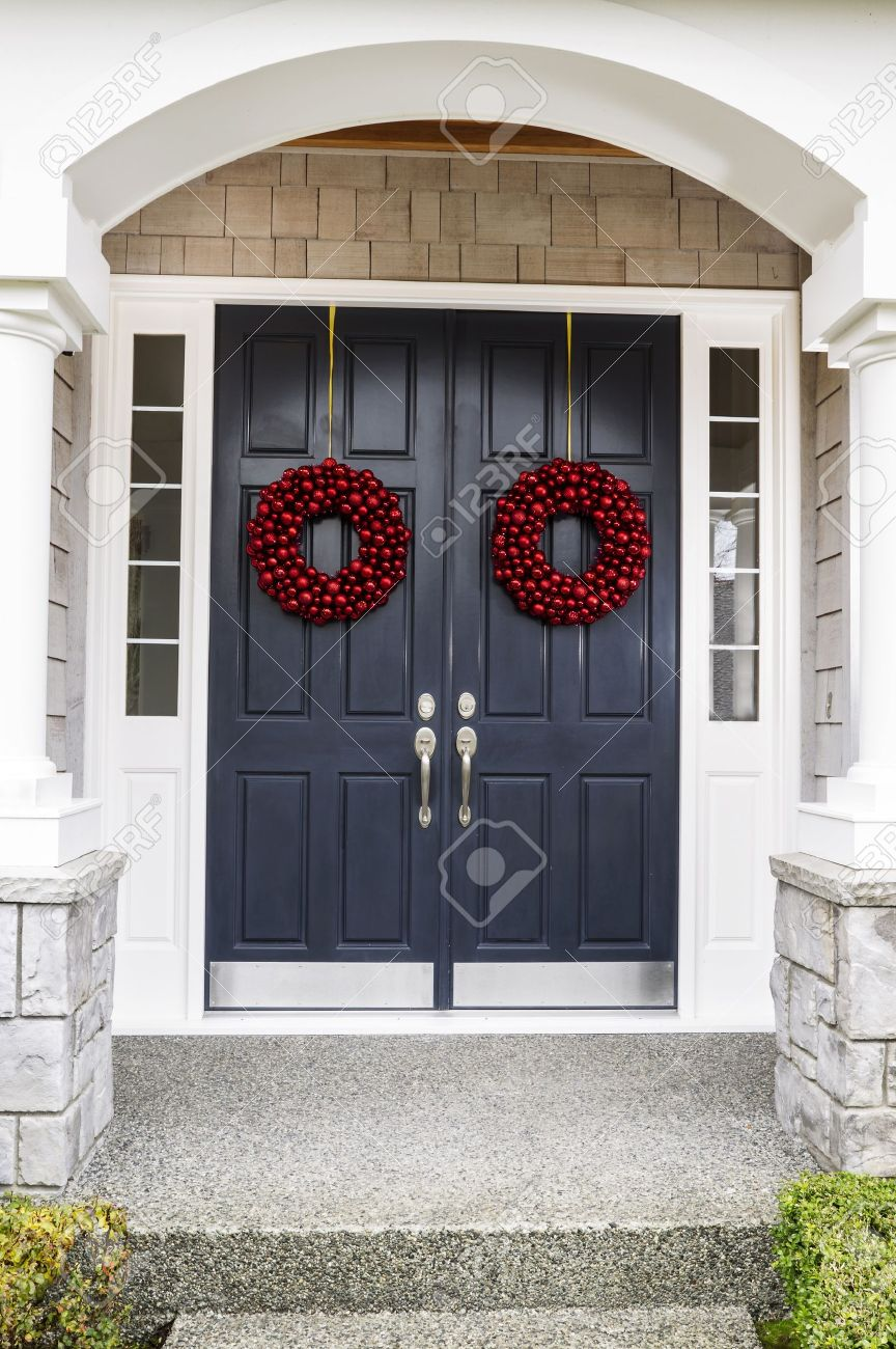 Front entrance of home door decorated with red ball wreaths for the holiday Stock Photo - 16587615