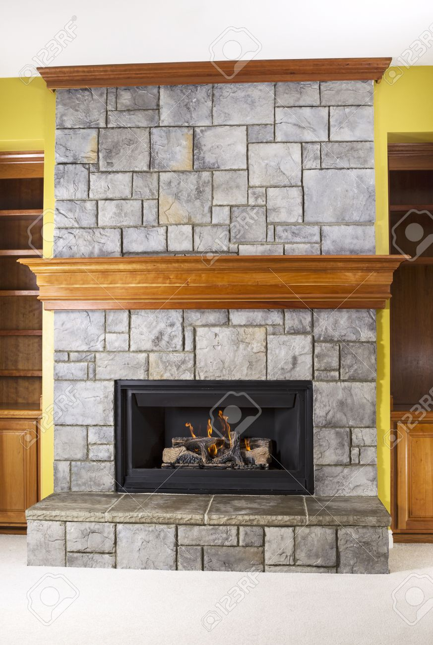natural gas fireplace built with stone and wooden mantels in