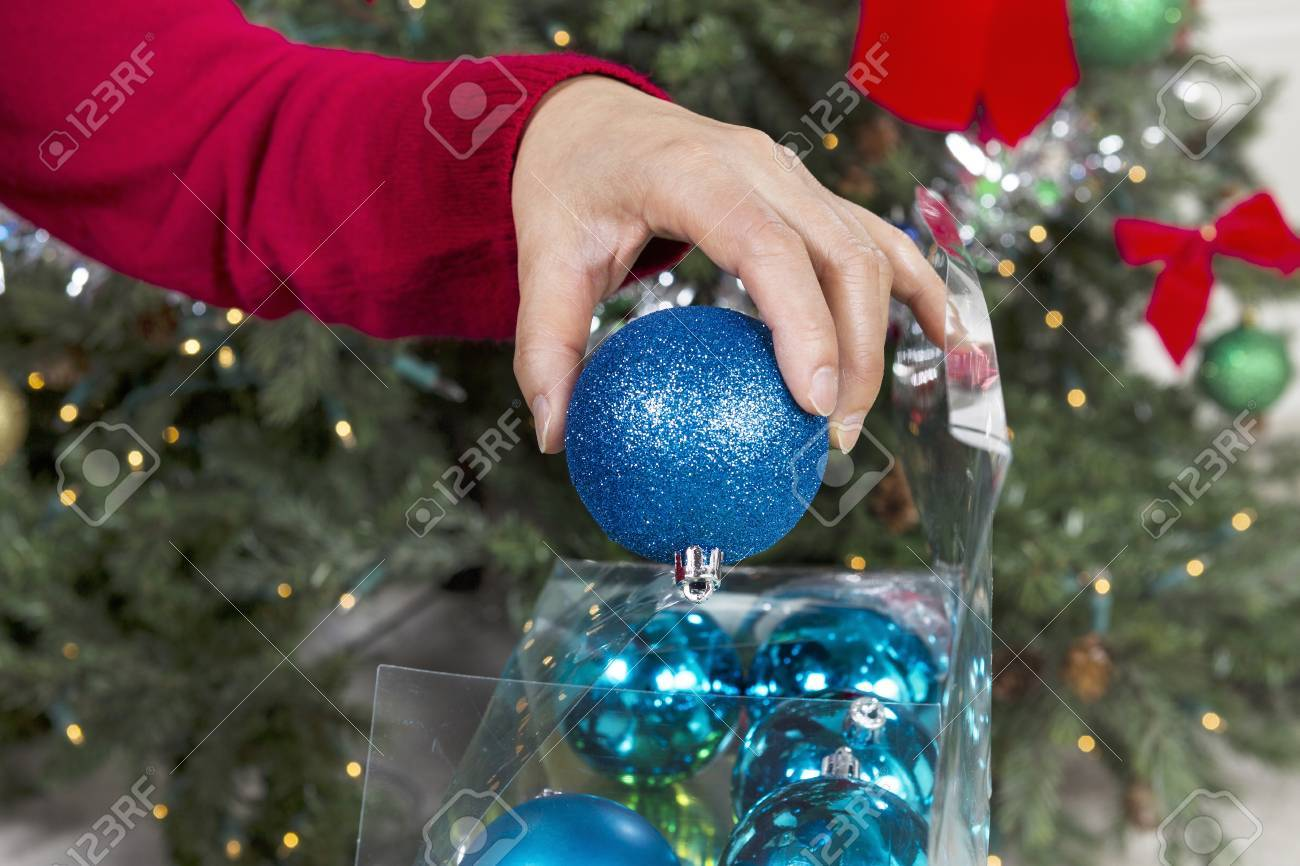 Female Hand Putting Away Holiday Ornaments To End The Season With Christmas  Tree In Background Stock