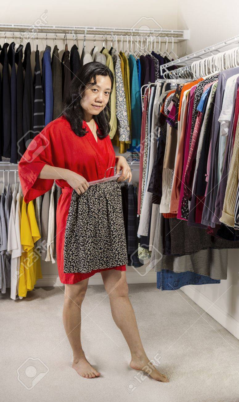 full vertical portrait of mature asian woman, dressed in red.. stock