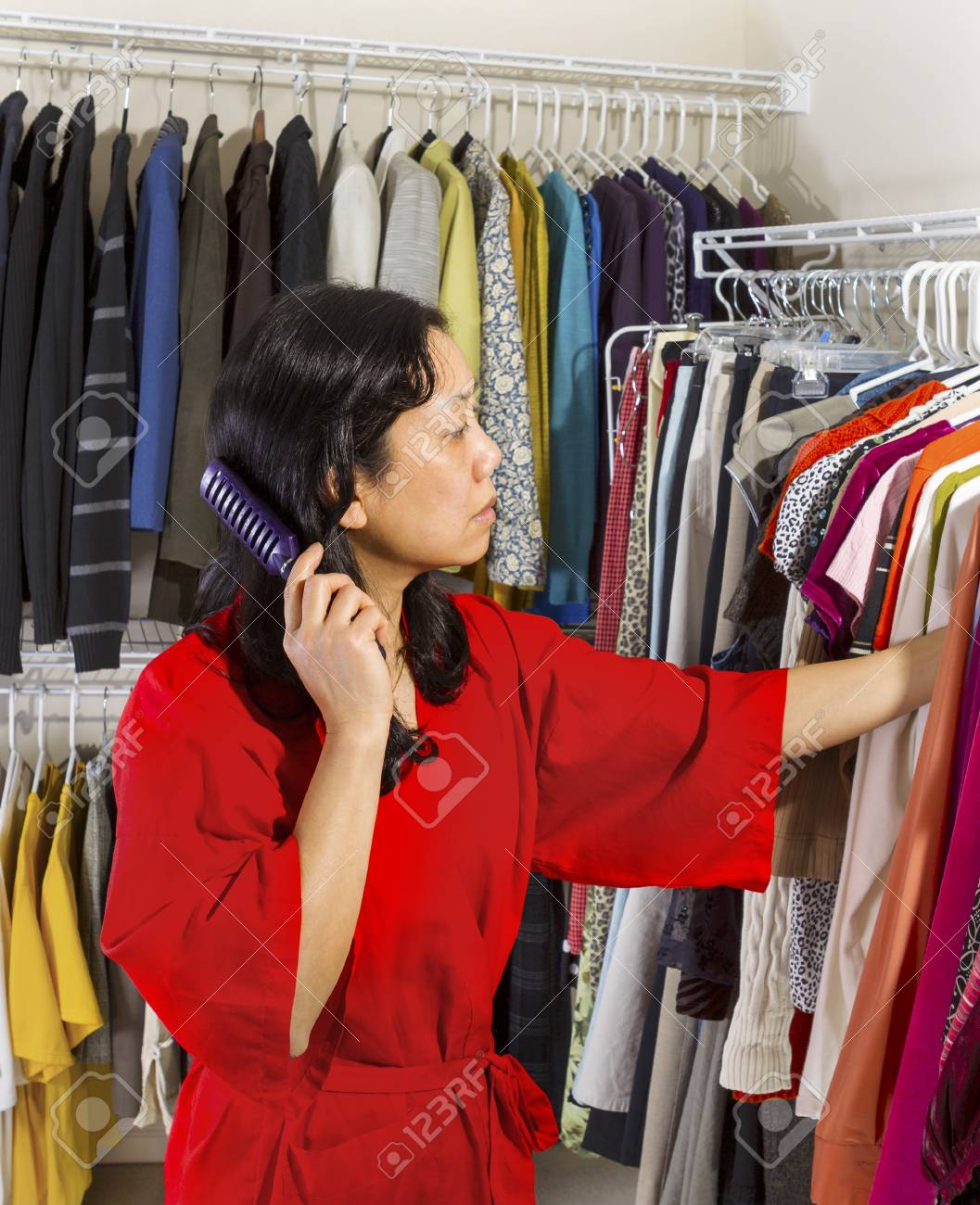 Vertical portrait of mature Asian woman, dressed in red bath robe, in walk-in closet combing her hair while looking at her hanging clothes Stock Photo - 17538640