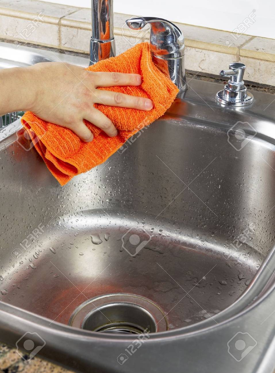 Vertical photo of female hand drying off kitchen sink with microfiber towel Stock Photo - 18061066