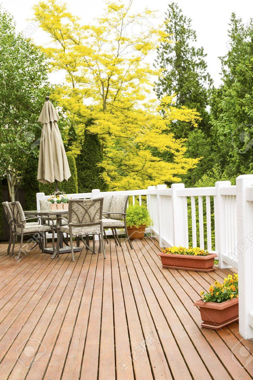 Vertical Photo Of A Large Outdoor Natural Cedar Deck With Patio Furniture  And Bright Yellow And