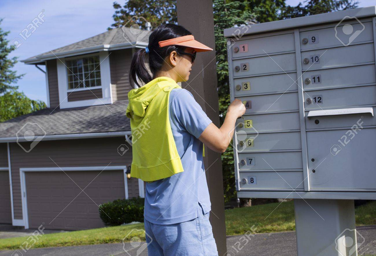 Horizontal photo of a mature woman checking her mailbox with a Northwest American home in the background Stock Photo - 21122109