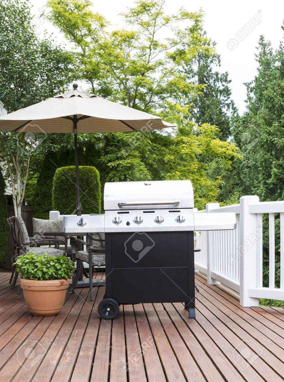 Stock Photo   Vertical Photo Of Large Barbecue Cooker On Cedar Deck With  Patio Furniture And Trees In Background
