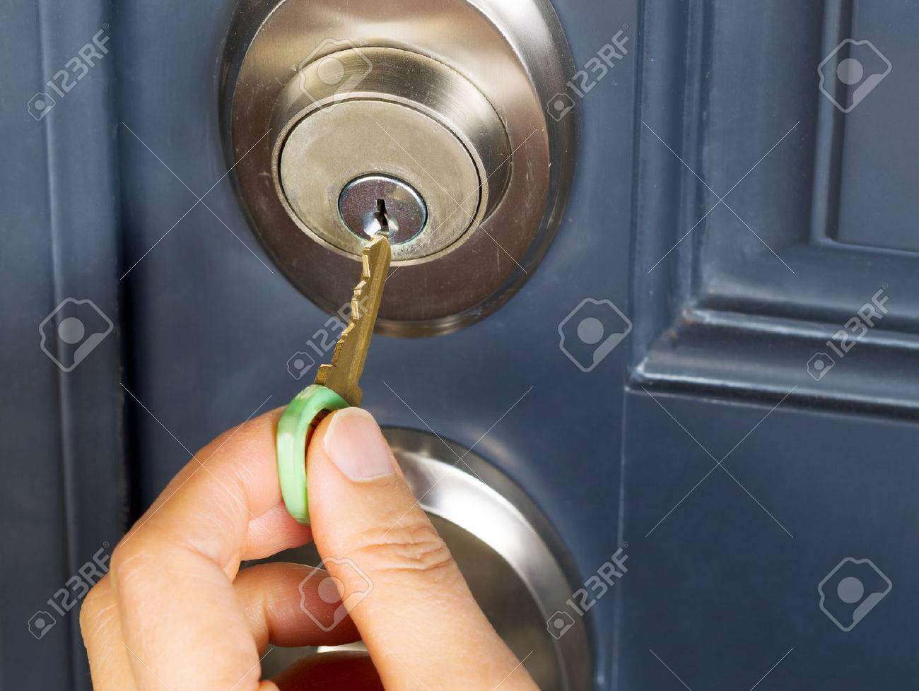 Female Hand Putting House Key Into Front Door Lock Of House Stock Photo    23687182