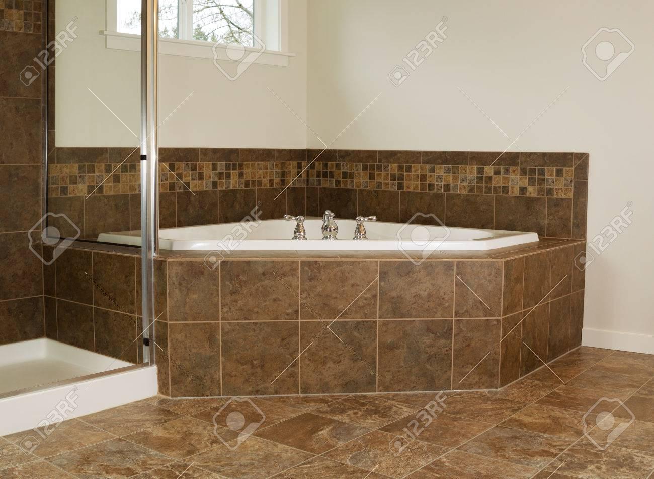 Photo horizontale de grande baignoire dans salle de bain avec douche et  fenêtres partielle