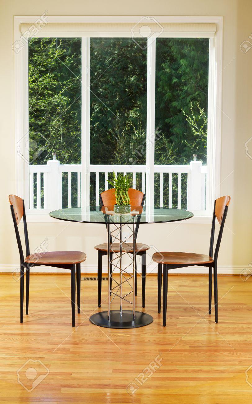 Photo verticale de la petite salle à manger avec parquet en chêne rouge,  table en verre, chaises en bois, bambou et de grandes fenêtres avec des ...