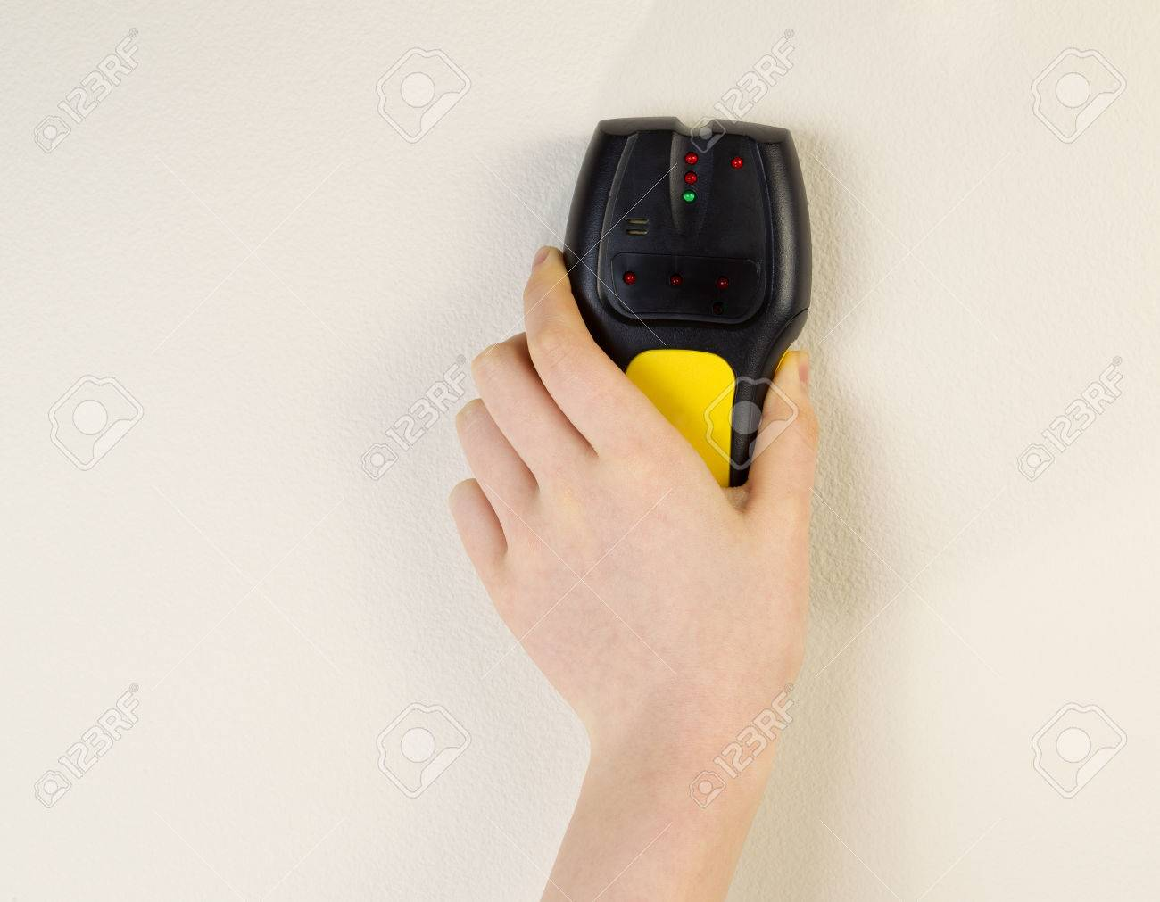 Photo of female hand holding stud finder against interior home white wall - 28101788