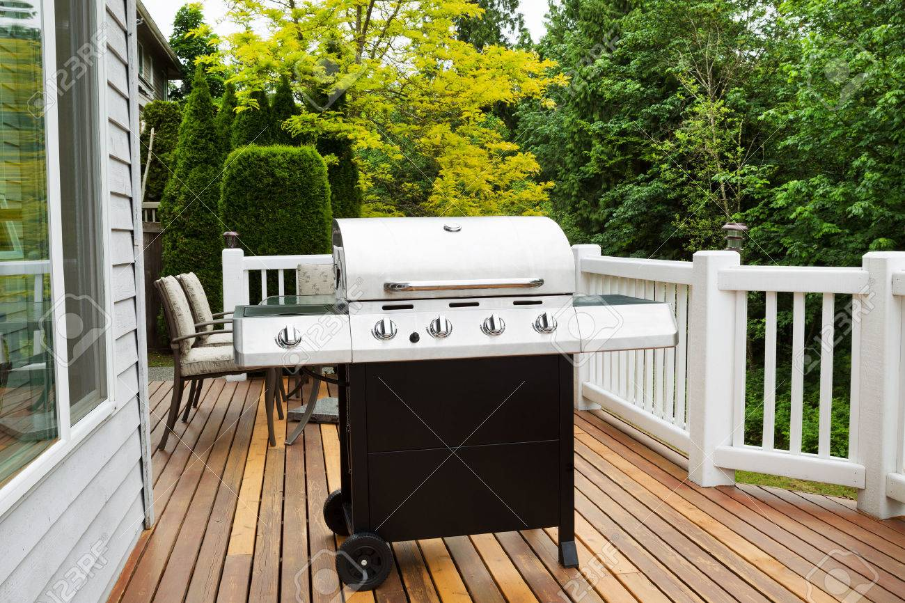 Closeup Horizontal Photo Of BBQ Grill On Open Cedar Patio With Seasonal  Trees In Full Bloom