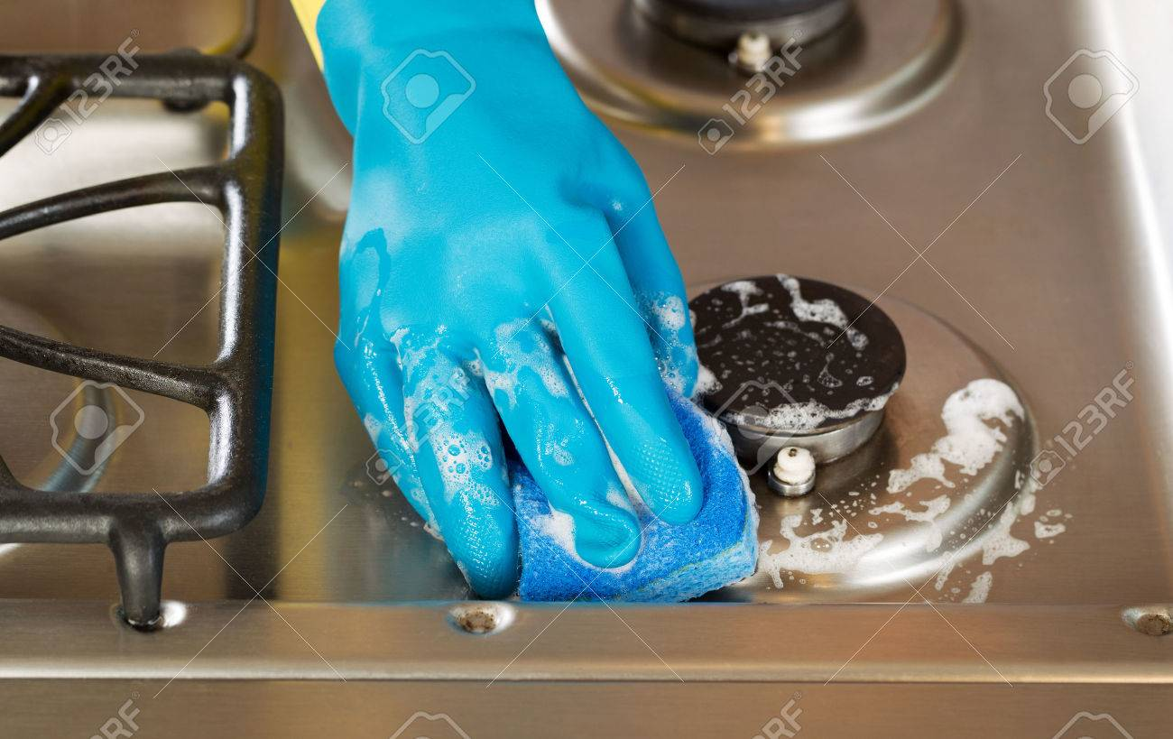 Closeup horizontal image of hand wearing rubber glove while cleaning stove top range with soapy sponge - 29603973
