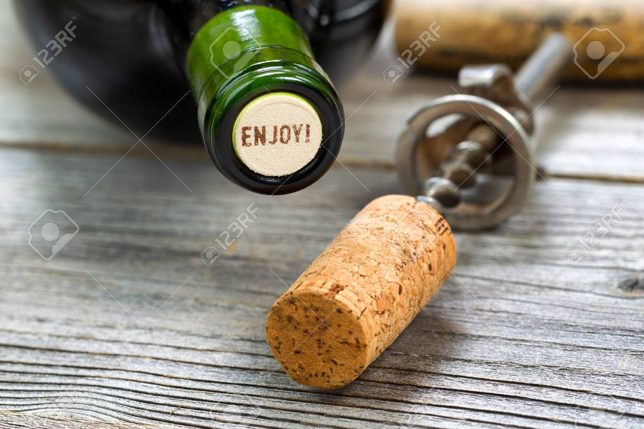 Close up shot of top of wine bottle cork, focus on the words enjoy, with rustic opener in background. Horizontal format layout. - 38656328