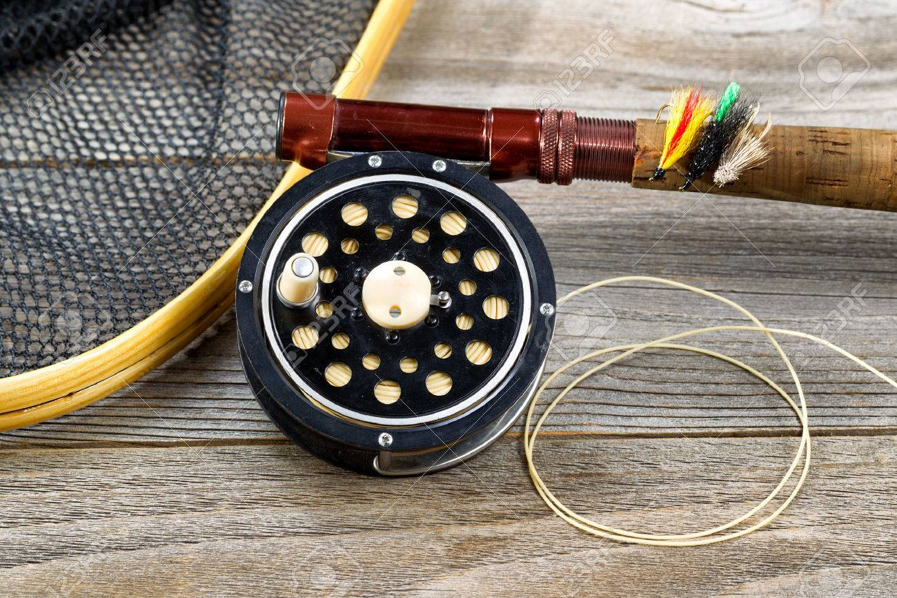 Close up of an antique fly fishing reel, rod, landing net and artificial flies on rustic wood. Layout in horizontal format. - 38661762
