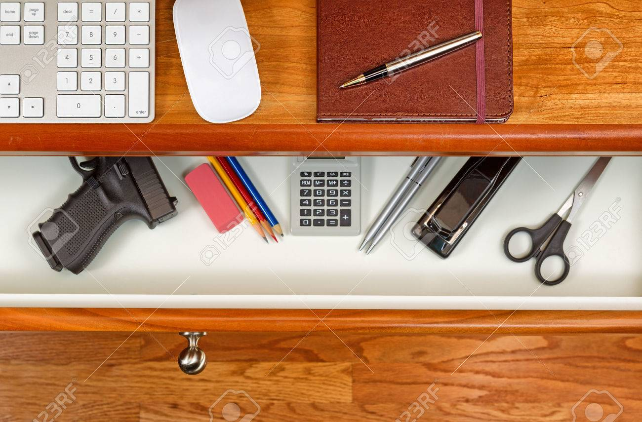 High Angle Shot Of Open Desk Drawer With Concealed Personal Weapon