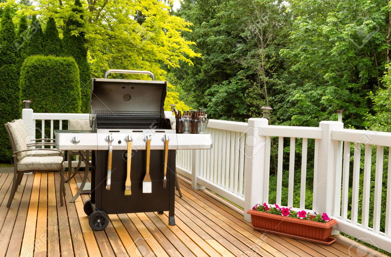 Photo of a clean barbecue cooker with cookware and cold beer in bucket on cedar wood patio. Table and colorful trees in background. - 40538570