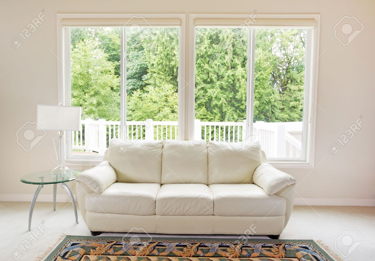 clean family room with white leather couch and large windows showing bright green trees in background