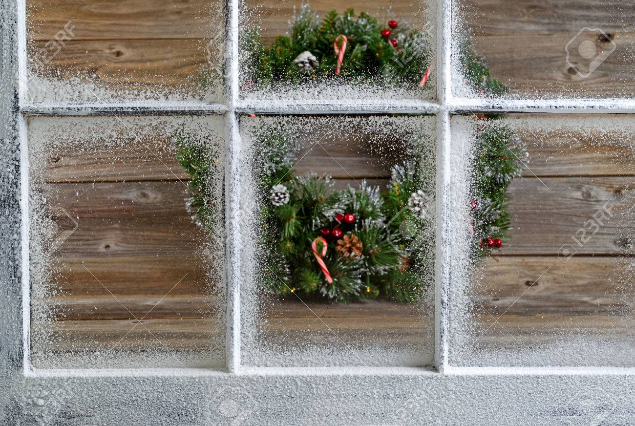 Snow Covered Window With Decorative Christmas Wreath On Rustic Wooden Boards In Background Focus