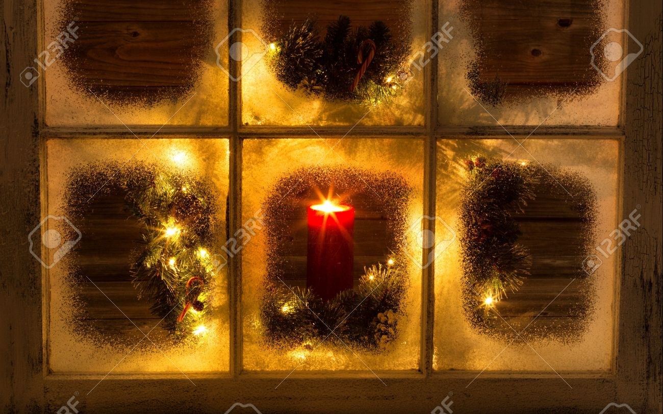 Snow covered window with glowing candle and decorative Christmas wreath on window with rustic wood in background. - 42355620