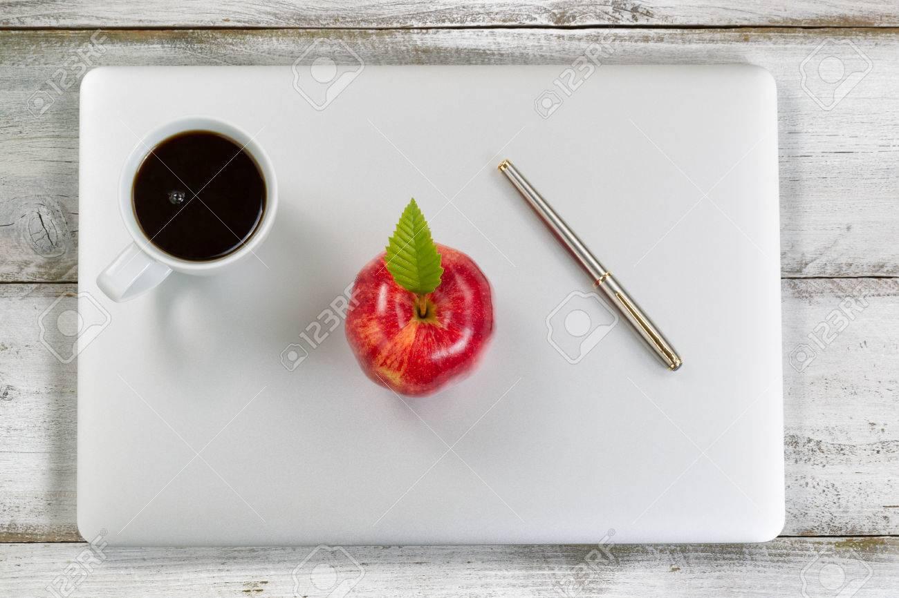Pomme rouge café et stylos argent sur le dessus de lordinateur