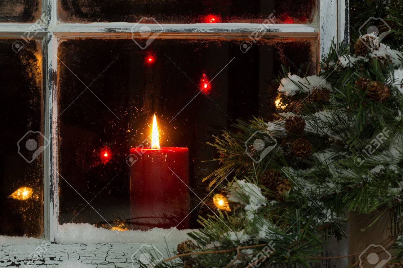 Close up of a red candle, selective focus on flame and top part of candle, glowing in window with pine tree and snow outside. Christmas concept. - 45219114