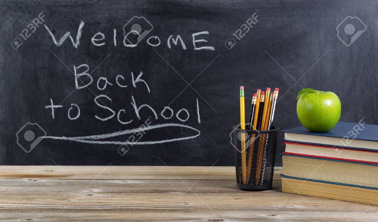 Old wooden desktop with basic school supplies and welcome back to school text on blackboard for students. Layout in horizontal format. - 47033606