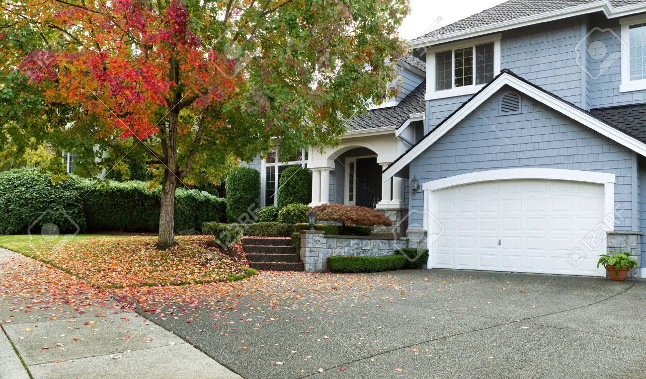 Front view of modern residential home during early autumn season in Northwest of United States. Maple trees beginning to change leaf colors. - 47034072