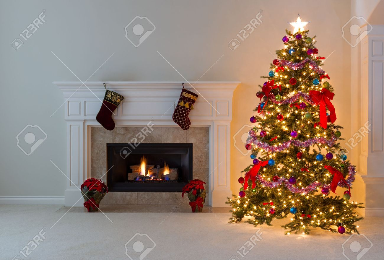 Christmas Tree In Living Room bright christmas tree and glowing fireplace in living room. stock