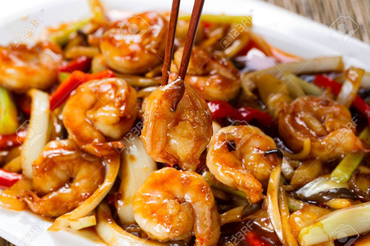 Close up front view of a curry shrimp, selective focus on single piece in chopsticks, with fresh peppers on onion in background. - 49920143