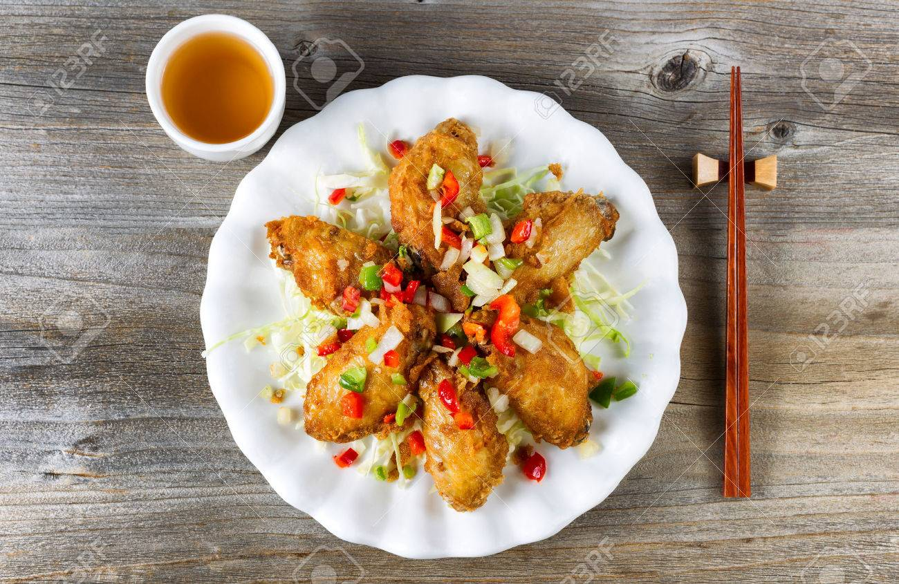 Top view of fried Asian style chicken wings in white plate with garnishes. Green tea and chopsticks in holder. Rustic wooden boards underneath. - 50228692