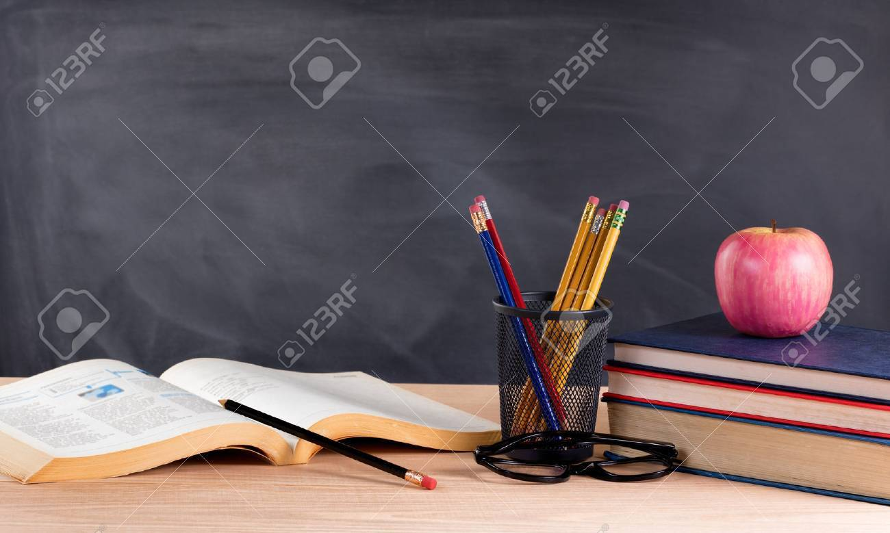 Desktop with books, pencils, apple, reading glasses and blank blackboard in background. Selective focus on front part of desk objects. - 50746560