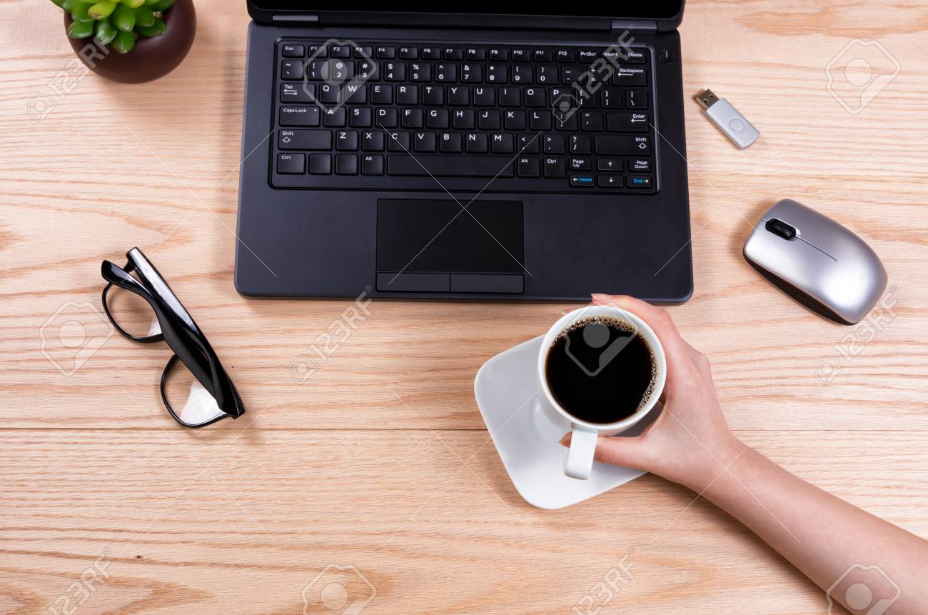 Vista dallalto della mano tenendo la tazza di caffè con il computer