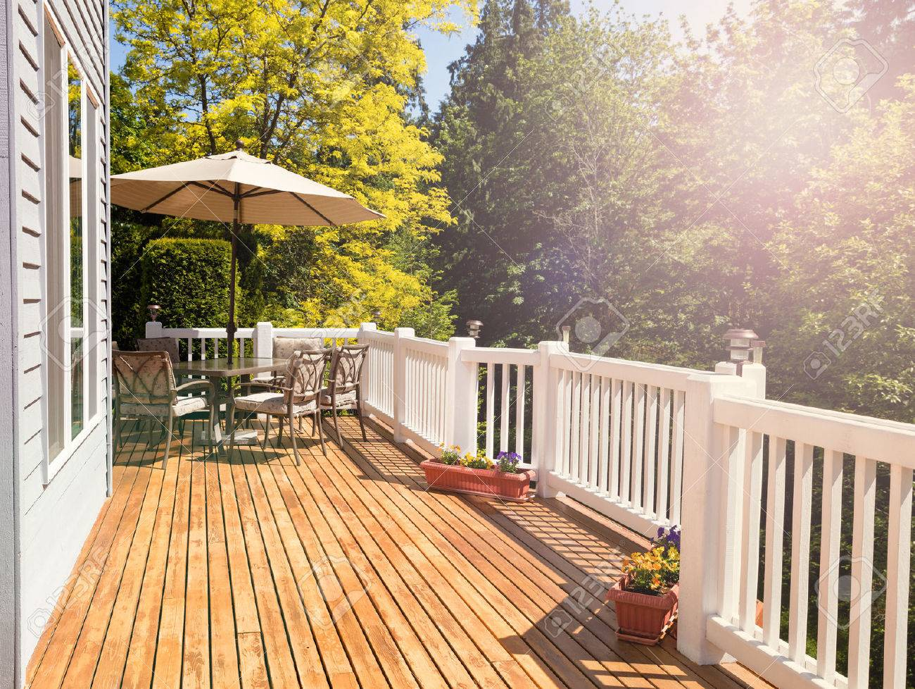 Afternoon bright daylight on outdoor home cedar deck with furniture and open umbrella. Light effect applied to image. Horizontal layout. - 56381768