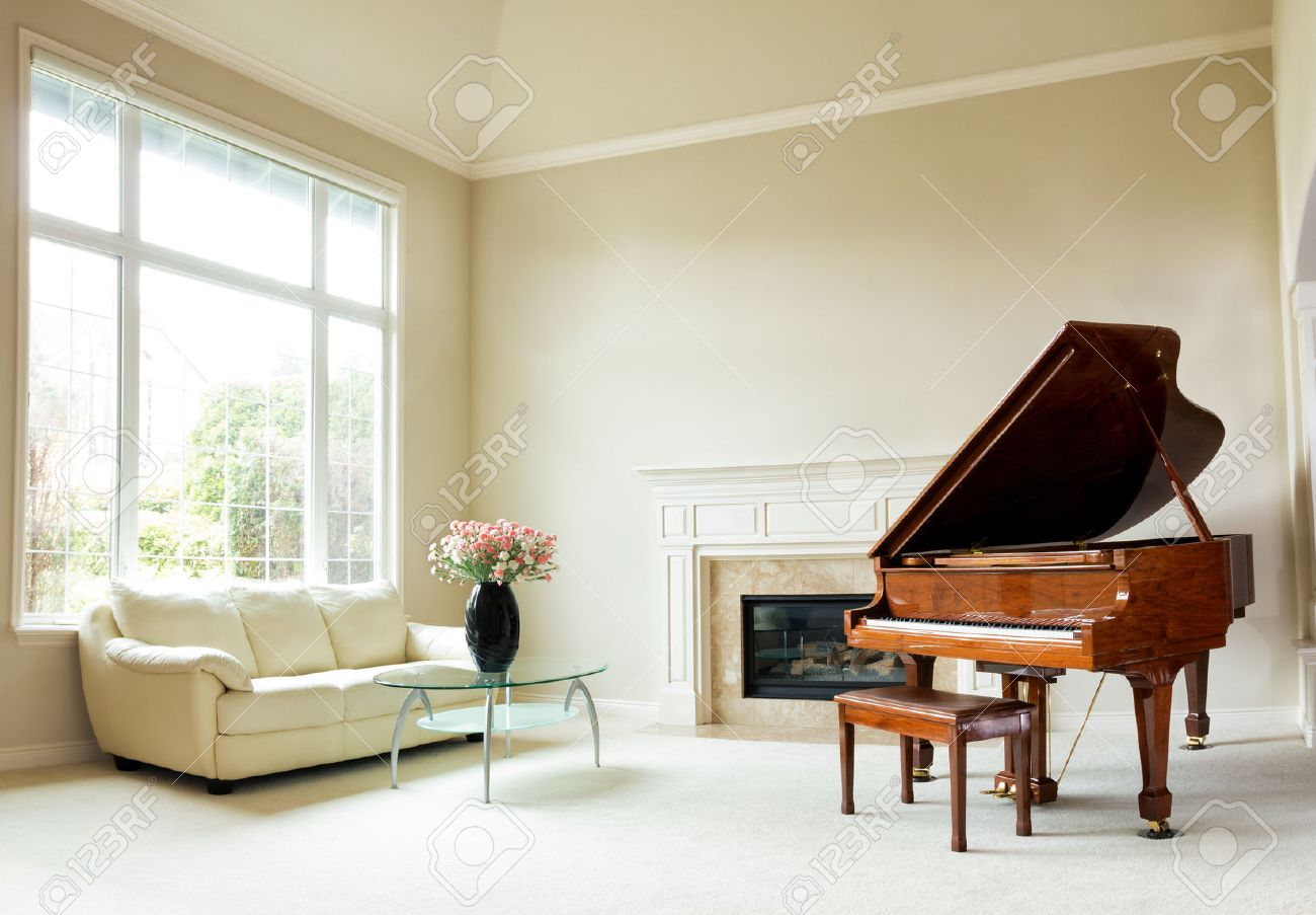Living room with grand piano, fireplace, sofa and large window with bright daylight coming through. - 57741833