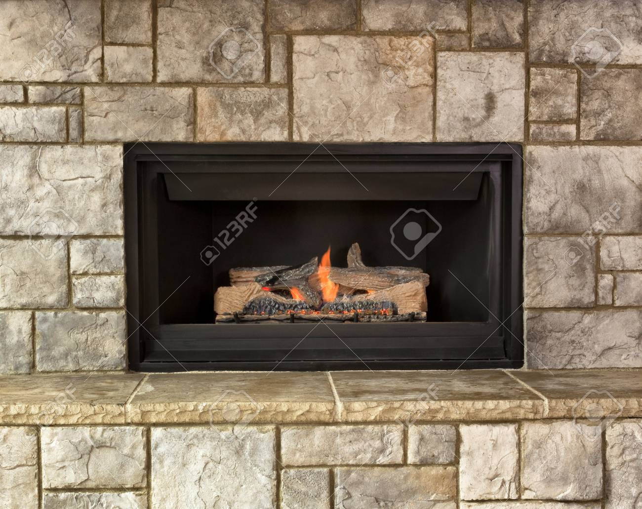 Burning natural gas fireplace surround by stone - 64479994