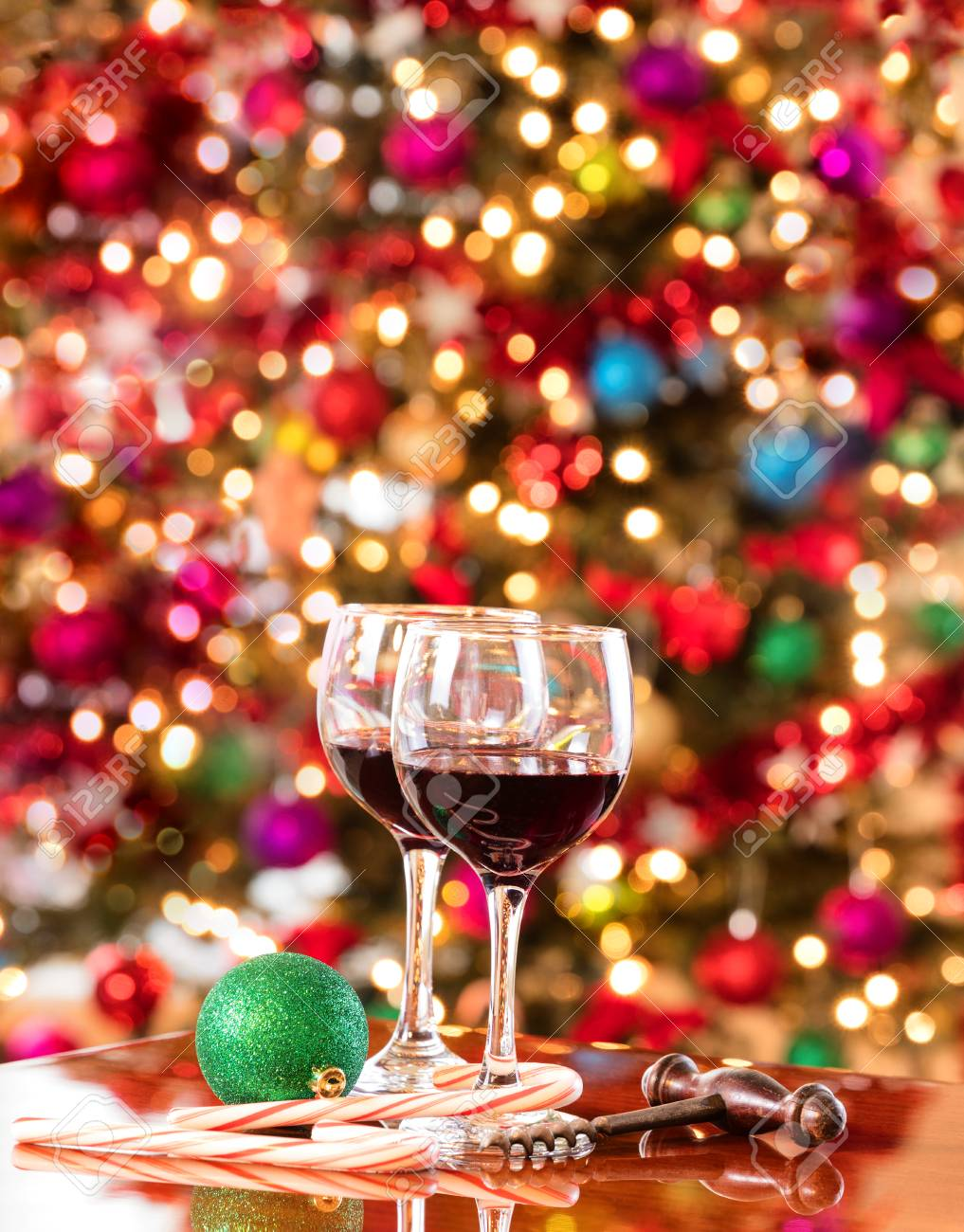 Red Wine On Mahoney Table With Bright Christmas Tree Lights In Background Vertical Format Layout
