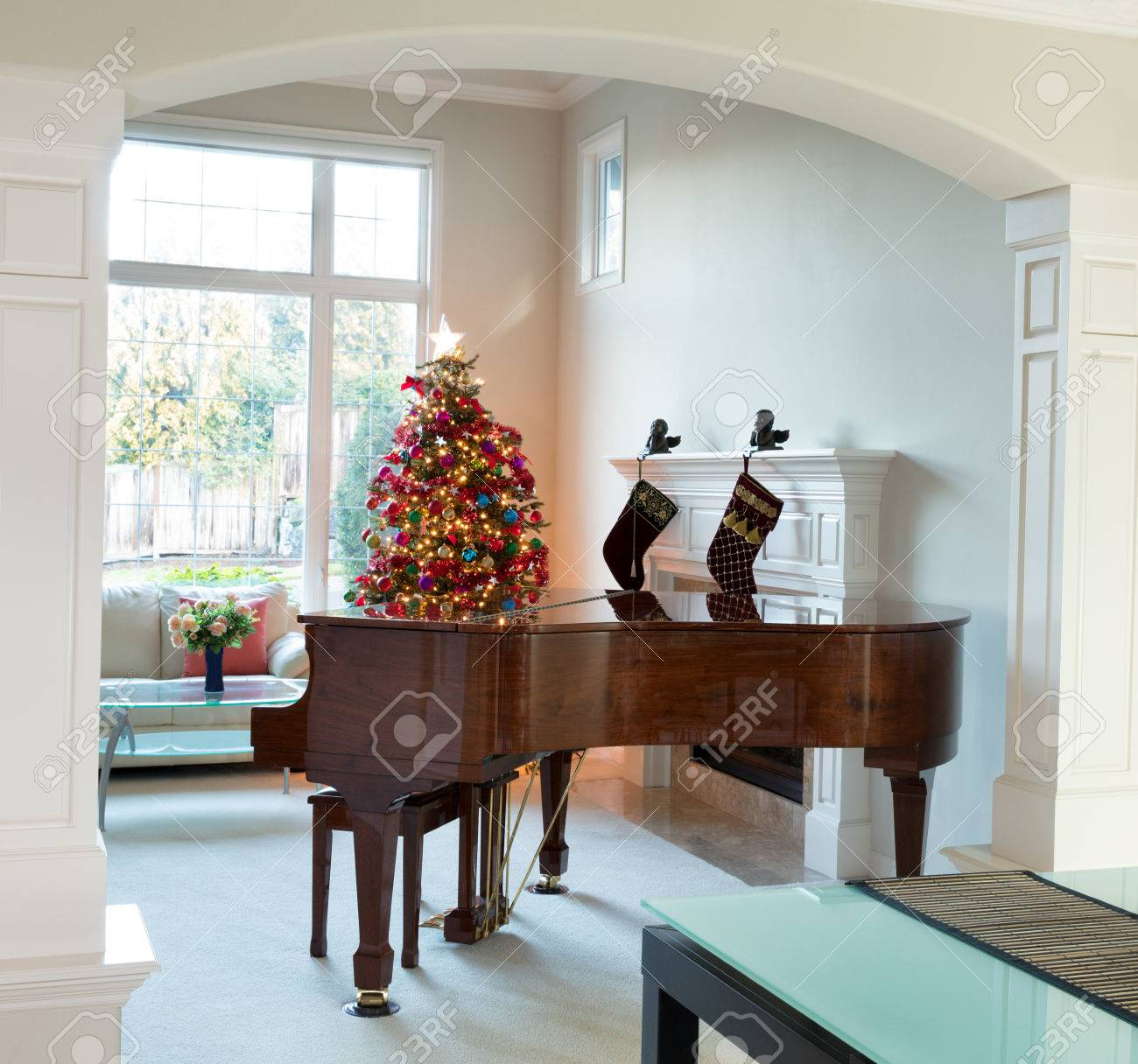 Living Room Entrance With Grand Piano Decorated Christmas Tree And Large Daylight Window In Background