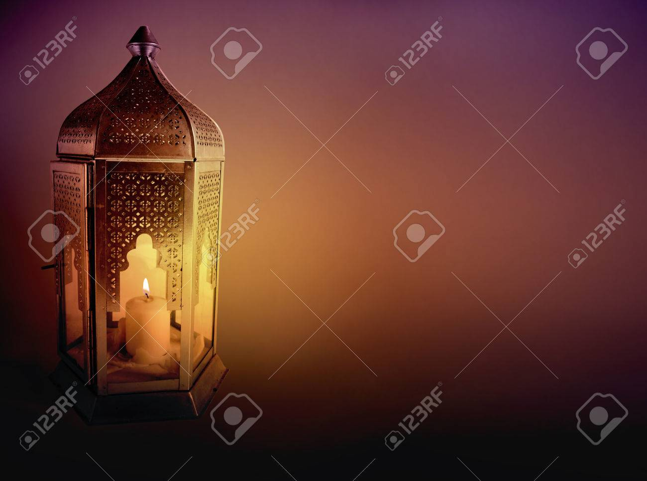 Ornamental Arabic lantern with burning candle glowing at night. Greeting card, invitation for Muslim community holy month Ramadan Kareem. Dark background with a lot of empty space. - 78069186