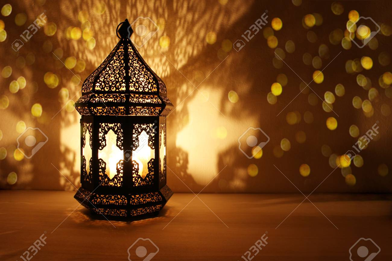 Ornamental Arabic lantern with burning candle glowing at night and glittering golden bokeh lights. Festive greeting card, invitation for Muslim holy month Ramadan Kareem. Dark background. - 98756343