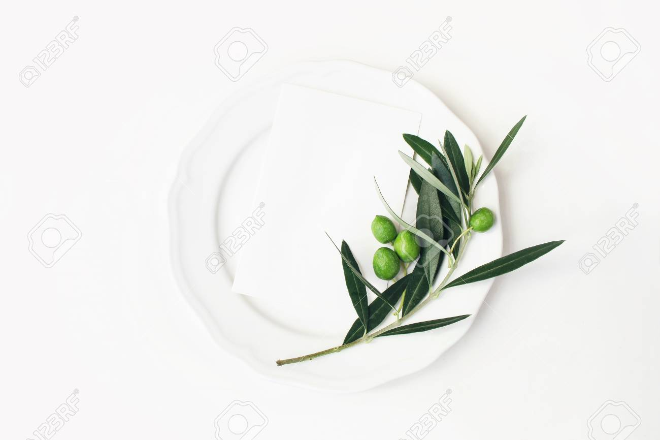 Festive table summer setting with olive leaves, branch and fruit on porcelain plate. Blank paper card mockup scene. Mediterranean wedding or restaurant menu concept. Flat lay, top view. - 117352090