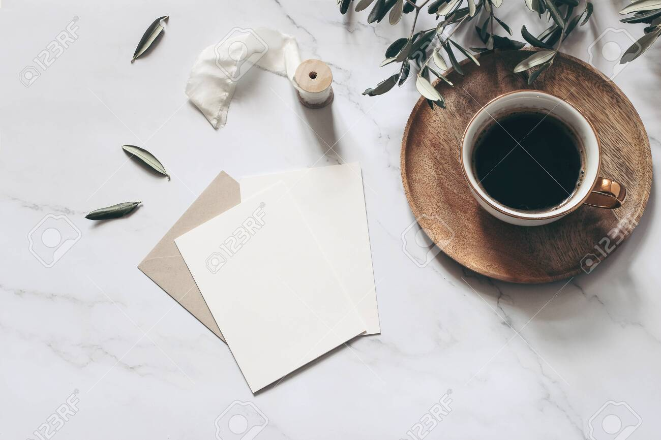 Summer wedding stationery mock-up scene. Blank greeting cards, wooden plate, envelope, ribbon, cup of coffee and olive branches. White marble stone table background. Feminine flat lay, top view. - 142609580