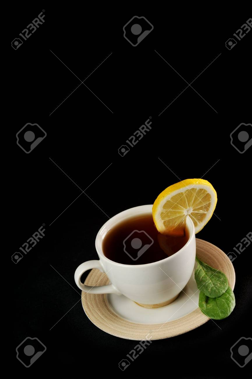 full cup of tea with lemon and  greens  leaves on  black Stock Photo - 6492004