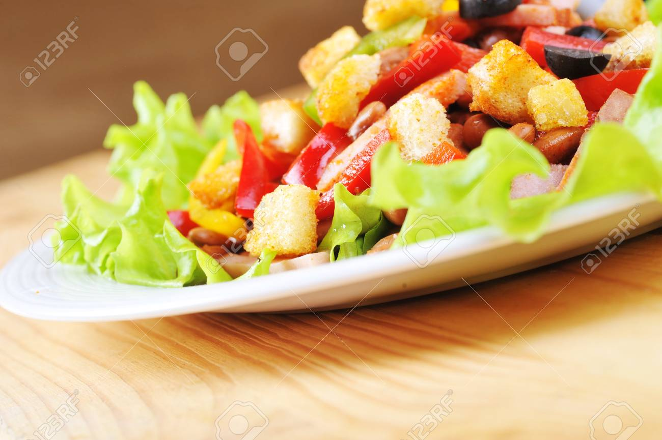 Fresh and tasty salad  on plate, wooden table Stock Photo - 8178438