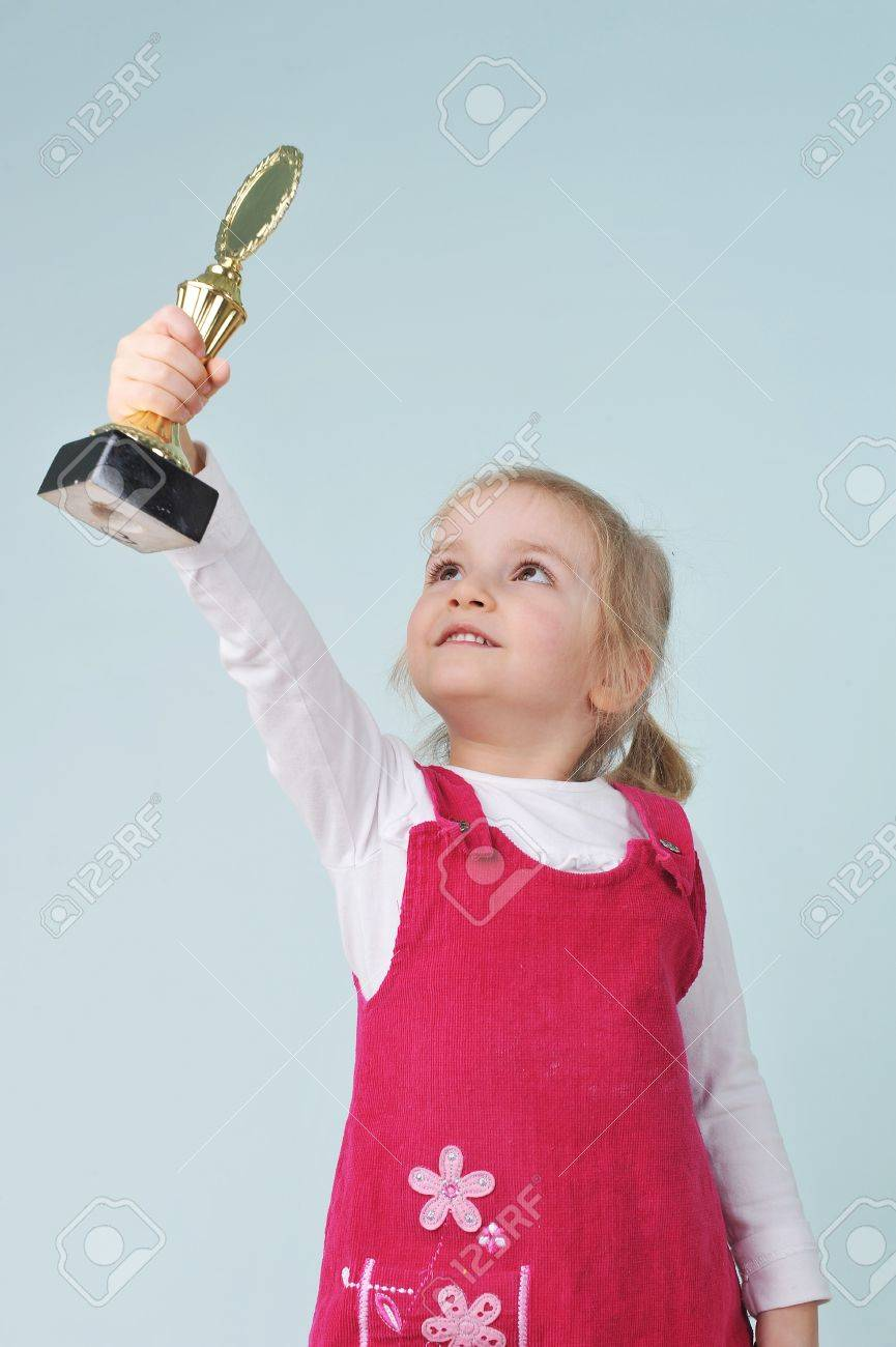 lovely blond little girl with champion cup Stock Photo - 9718529