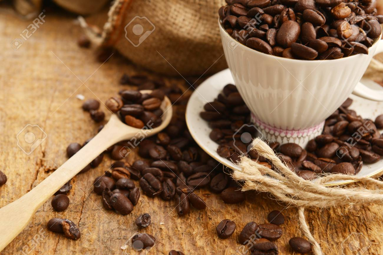 Roasted coffee beans with cup on jute hessian background Stock Photo - 17780596