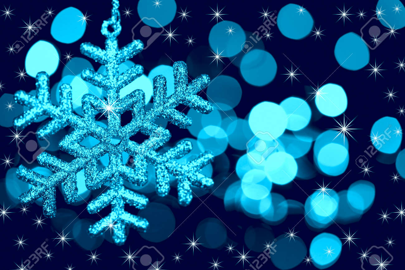 Christmas decoration snowflake  on defocused lights and stars background / blue toned Stock Photo - 11272335