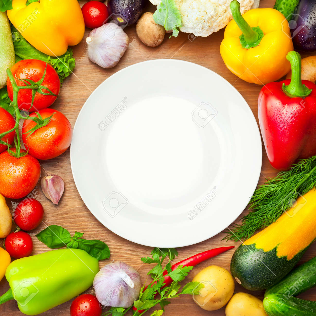Fresh Organic Vegetables on wooden Table Around White Plate   with copy space for your text Stock Photo - 20294440