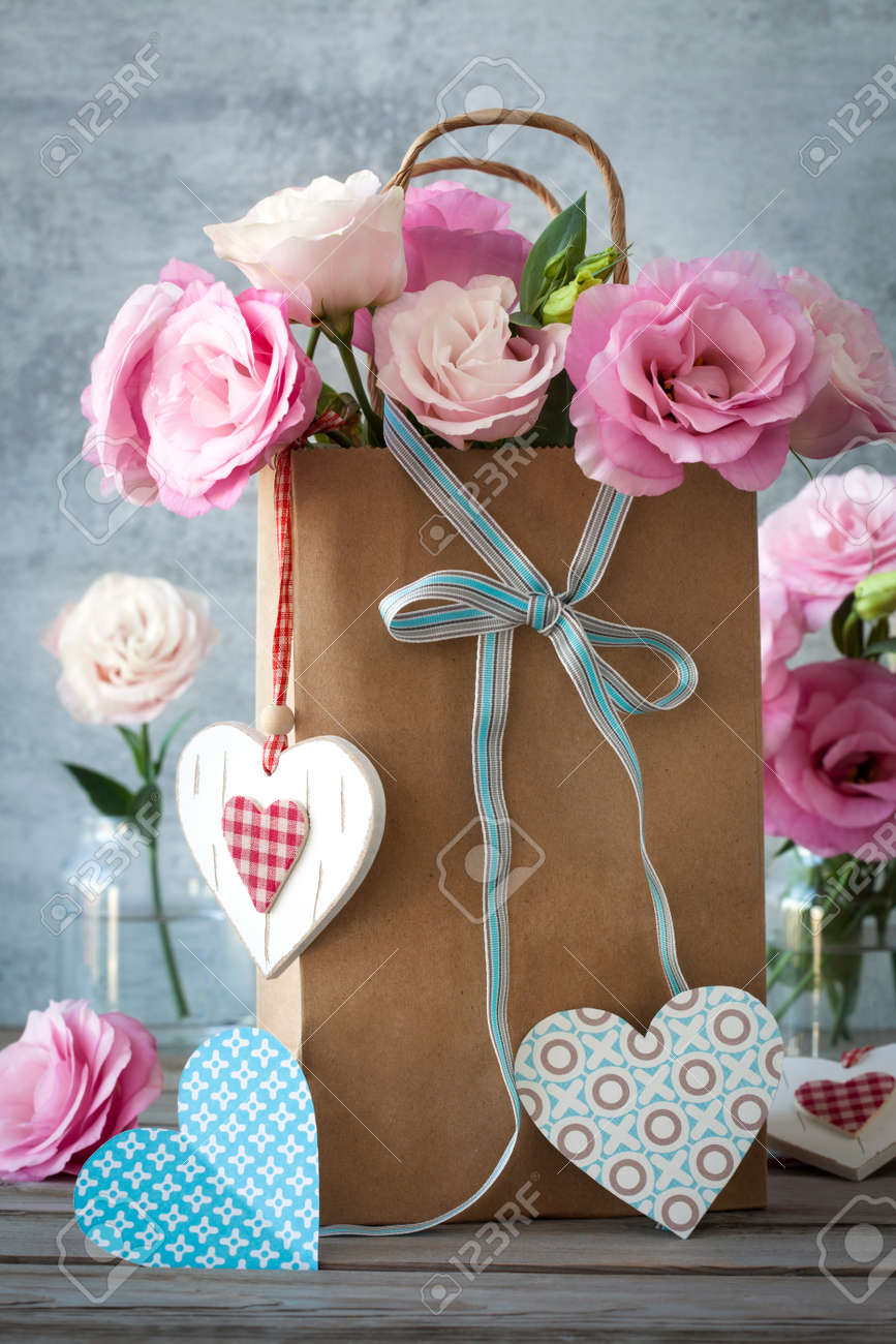 St. Valentines Day background with pink flowers, blue bow and paper and wooden hearts - 35356231