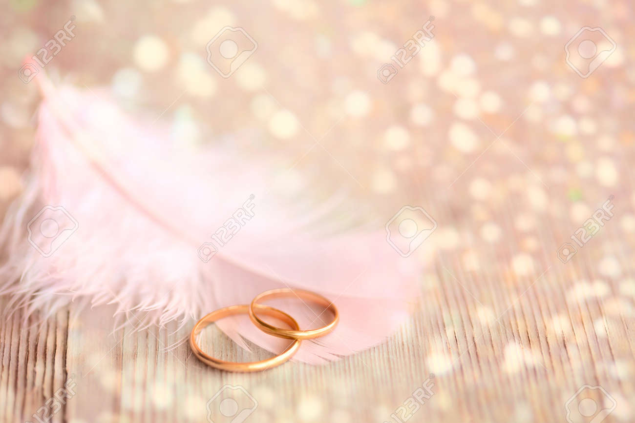 Wedding Background with Gold Rings, pink feather and golden magical lights - 45139668